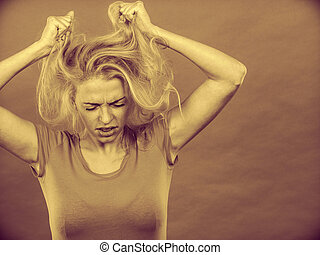 Frustrated woman holding her damaged blonde hair