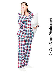 Yawning sleepy woman in warm pajamas holds ready pillow on...