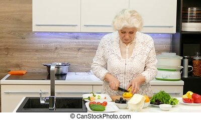 Happy Grandmother Making Salad Of Fresh Vegetables