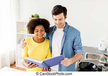 happy couple with cooking book at home kitchen - people and...