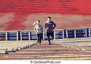 couple running upstairs on stadium - fitness, sport,...