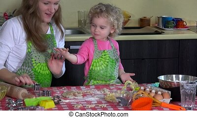 Excited little daughter girl making cookies with her beautiful mother