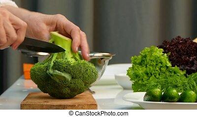 Female Chef Cutting Fresh Broccoli On Carving Board