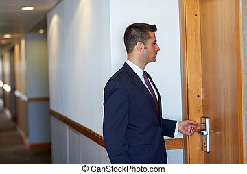 businessman with keycard at hotel or office door - business,...
