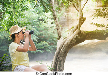 Pretty Asian woman looking with  Binoculars front of waterfall.