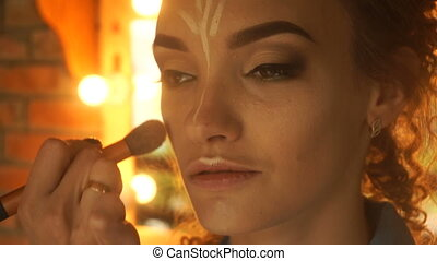 makeup artist deals concealer on the face of a young...