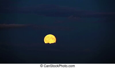 The full moon moves on the sky through clouds,