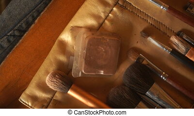 girl picks up the shadow brush for makeup - a young girl...