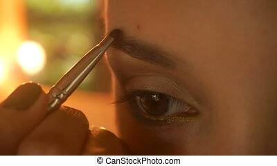young girl colors eyebrow brush close-up