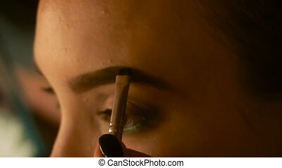 makeup artist paint eyebrows young woman close-up