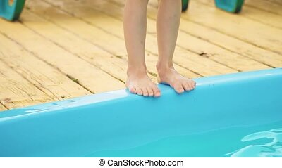 Little girl jumping to the swimming pool