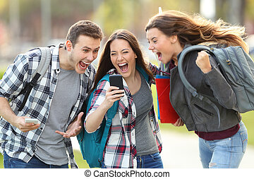 Excited students receiving good news on phone - Front view...