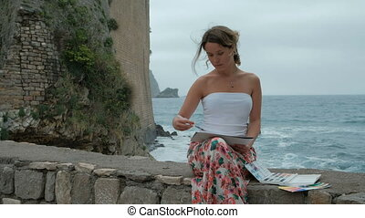 Beautiful Young woman artist paints a seascape on the beach in windy weather