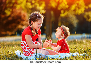 Two girls playing in summer park.