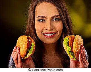 Woman eating hamburger. Girl bite of very big burger