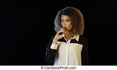 Woman is standing in a dark room smoking an electronic...
