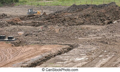 Bulldozer aligns the large pile of clay outdoors - Bulldozer...