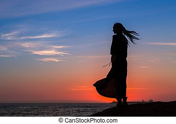 Silhouette of beautiful woman in dress on the seacoast during beautiful twilight.