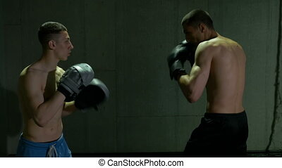 Two male kickboxing fighters training in boxing studio with concentration and determination