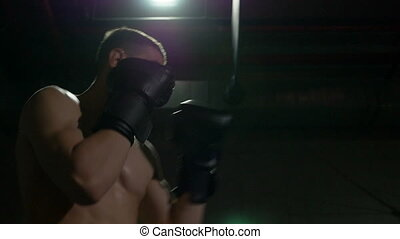 Kickboxer exercising boxing inside sport gym in slow motion