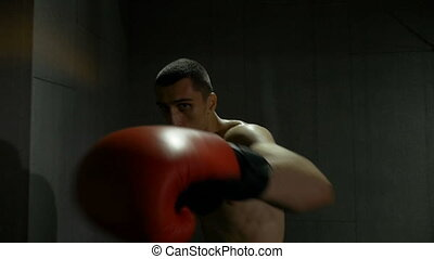 Slow motion of fighter training himself and hitting punches...