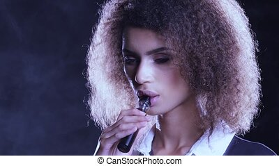 African american woman smokes an e-cigarette and lets smoke...