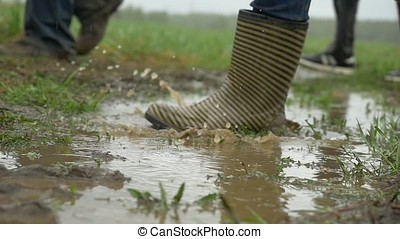 people in rubber boots are on the ground. Feet in rubber boots rain puddle. People in rubber boots go through a puddle