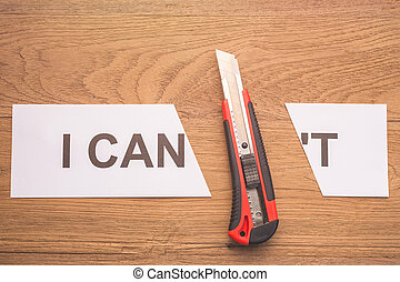 """Red cutter blade cutting word """"I CAN'T"""" in white paper on brown wooden plank"""