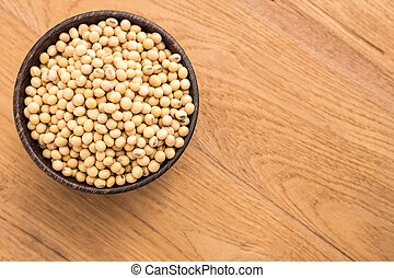 Soybean in wooden bowl put on wooden plank background - Top...