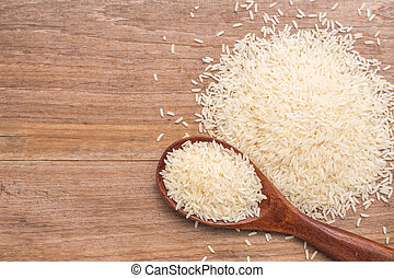Thai jasmine rice put on wooden plank background - Top view...