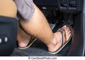 Right foot with flip flop shoe step on the accelerator in the modern car