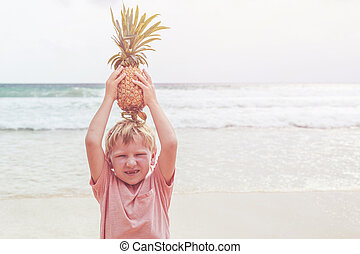 Caucasian boy from europe holding pineapple with happy and...