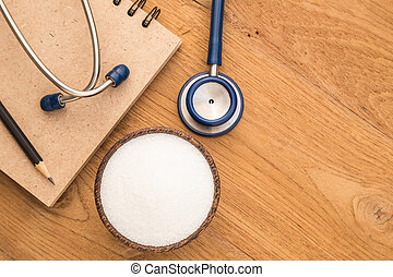 Blue stethoscope, sugar and note book on wooden plank...