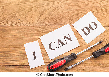"Screwdriver word ""I CAN DO"" in white paper on brown wooden plank"