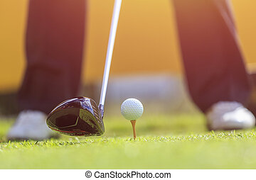 A man playing golf in green course. Focus on golf ball -...