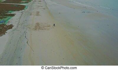 Flycam Follows Man Driving Motorcycle against Ocean Hills -...