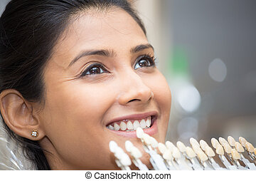 Shade guide to teeth, selection process - Closeup portrait...
