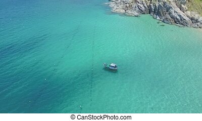 Boat Sails on Azure Ocean by Rocky Hill and Beach - Aerial...