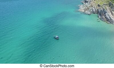 Flycam Approaches Boat Sailing on Ocean against Rocky Hills...