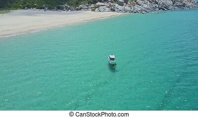 Flycam Approaches Boat Sailing on Azure Ocean by Sand Beach...