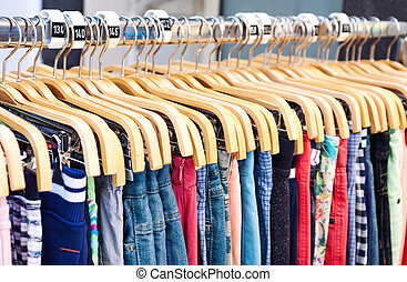 Multicolored casual clothing on wooden hangers in the store