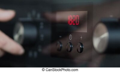 Woman engages the oven to start cooking, close-up - woman...