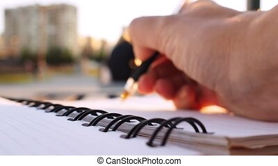 Woman writing in diary, outdoor, close-up. Goal, make a plan or concept of their business