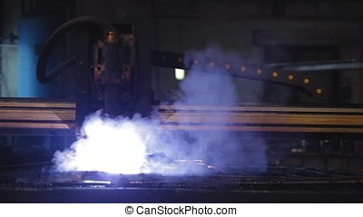 Plasma cutting at the factory, the machine cuts metal with...