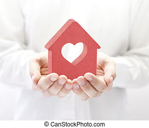 Small red house with heart in hands