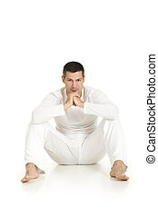 man dressed in white sitting on the floor