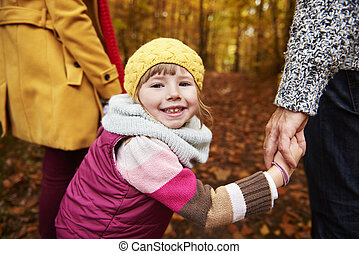 Smiley girl holding parents hands