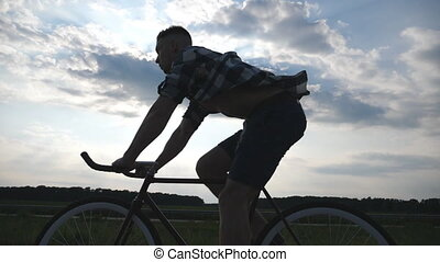 Silhouette of young man riding at vintage bicycle with beautiful sunset sky at background. Sporty guy cycling in the country road. Male cyclist riding fixed gear bike. Healthy active lifestyle Slowmo
