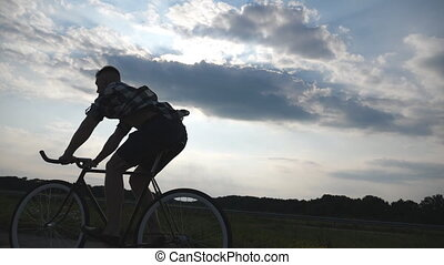 Silhouette of young man riding at vintage bicycle with beautiful sunset sky at background. Sporty guy cycling in the country road. Male cyclist riding bike. Healthy active lifestyle Slow motion