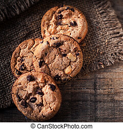 Chocolate cookies on dark napkin on wooden table. Closeup of...